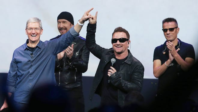 Apple CEO Tim Cook, left, and U2 singer Bono gesture during an Apple special event Sept. 9.