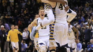 Marquette center Luke Fischer, center, is swarmed by teammates after making free throws in the final seconds of an NCAA college basketball game against Georgetown on Tuesday, March 1, 2016, in Milwaukee. Marquette defeated Georgetown 88-87. (AP Photo/Darren Hauck)