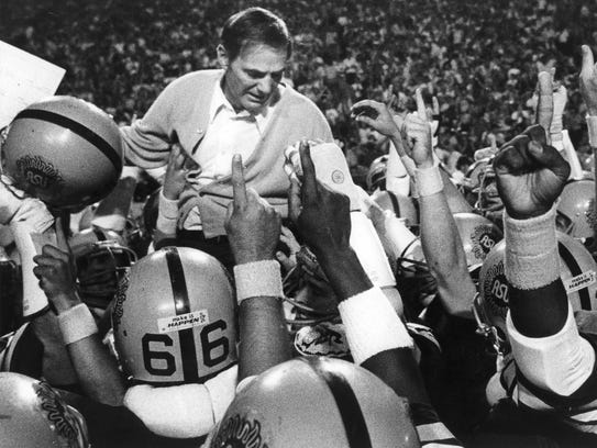 ASU players carry Frank Kush off the field after a