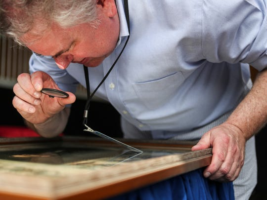 Appraiser Craig Flinner looks over a print during a quick appraisal at the traveling Antiques Roadshow event in the paddock of Churchill Downs Tuesday morning. May 22, 2018.