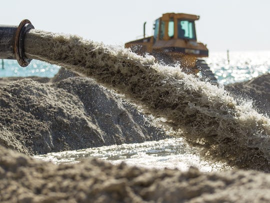 In this April 2013 file photo, sand is pumped onto South Marco Beach by a marine dredge as part of a beach renourishment and erosion control project on Marco Island.