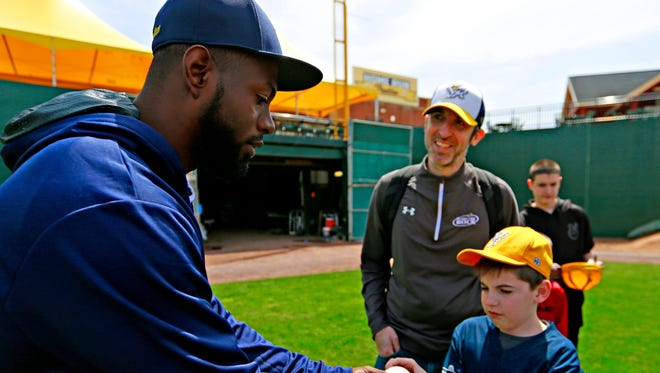 Melky Mesa is seen here last year signing a baseball for a young fan. Mesa will return to the York Revolution for the 2019 season.