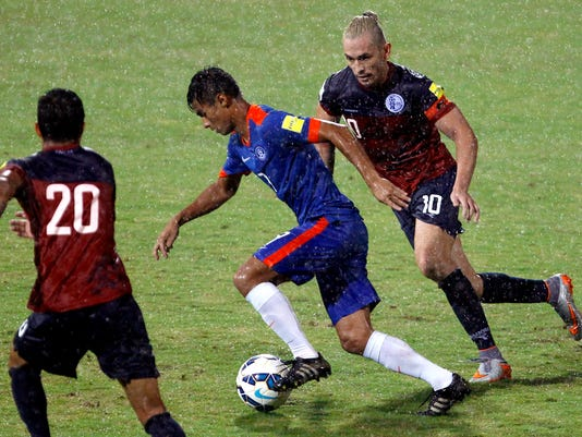 FILE - In this Nov. 12, 2015 file photo, Guam's captain Jason Cunliffe, right, and teammate Adolf DeLaGarza, left, chase India's Eugenson Lyngdoh as it rains during their 2018 FIFA World Cup qualifying soccer match in Bangalore, India. Less than two years after the team from tiny Guam drew international attention in the qualifying tournament for the 2018 World Cup, the football story in the northern Pacific island has turned to one of broken dreams. Prior to June 2015, the United States territory, which joined FIFA only in 1996, had lost its only two World Cup qualifiers with a combined score of 35-0. (AP Photo/Aijaz Rahi, File)