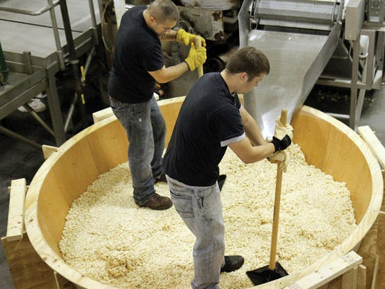 Noble Popcorn workers tamp down a popcorn mixture in