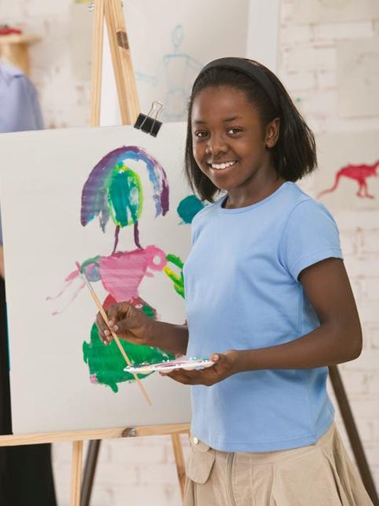 Smiling girl painting