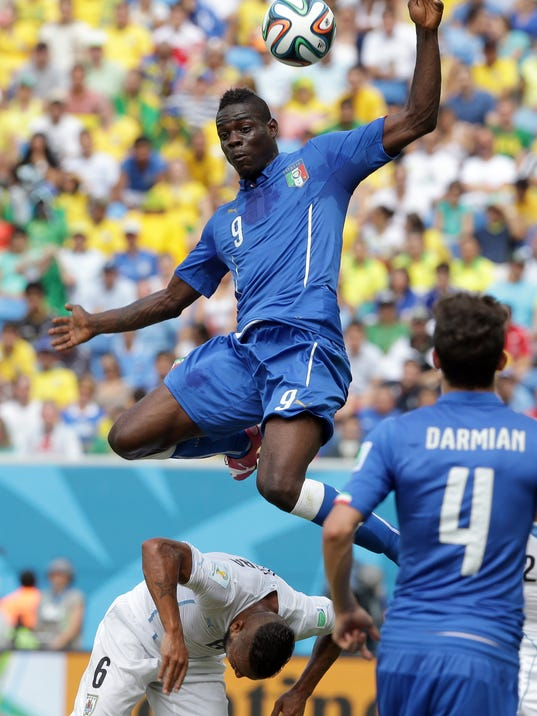 Italy's Mario Balotelli, top, collides with Uruguay's Alvaro Pereira, bottom, during the group D World Cup soccer match between Italy and Uruguay at the Arena das Dunas in Natal, Brazil, Tuesday, June 24, 2014. (AP Photo/Antonio Calanni)