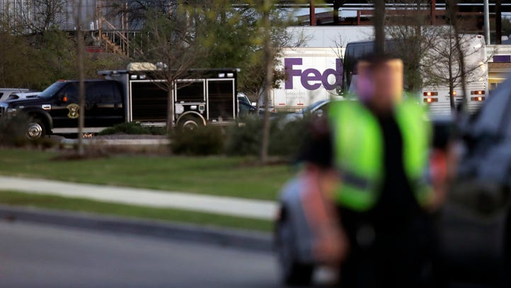 Emergency vehicles sit in front of a FedEx distribution