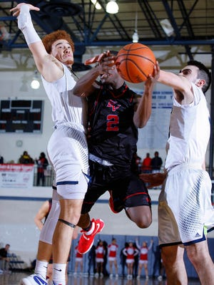 Everett's Nyreel Powell, center, drives for a layup between East Lansing's Deandre Robinson, left, and Noah Schon last month. Powell has boosted his scoring by roughly eight points this season for Everett.