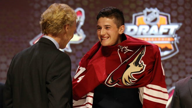 Brendan Perlini smiles as he puts on a team sweater after being selected as the number twelve overall pick to the Arizona Coyotes in the first round of the 2014 NHL Draft at Wells Fargo Center.