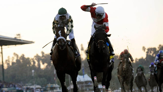 Brian Hernandez Jr., right, aboard Fort Larned, celebrates after finishing ahead of Mike Smith aboard Mucho Macho Man to win the Breeders' Cup Classic a year ago.
