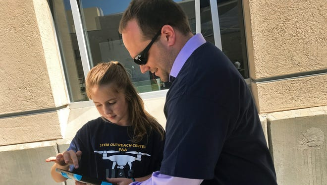 Maisy Thomlinson, who will be a fifth-grader at Hillrise Elementary in the fall, helps FAA representative Ben Bradley program a remote-controlled vehicle.