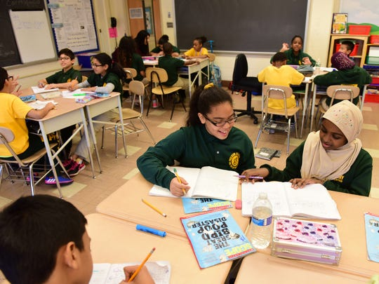 Center, Euribel Diaz, a 5th Grader at the Paterson Academy for the Gifted and Talented at Public School #28, works with a classmate in Mrs. Carrasquillo, English Language Arts class.