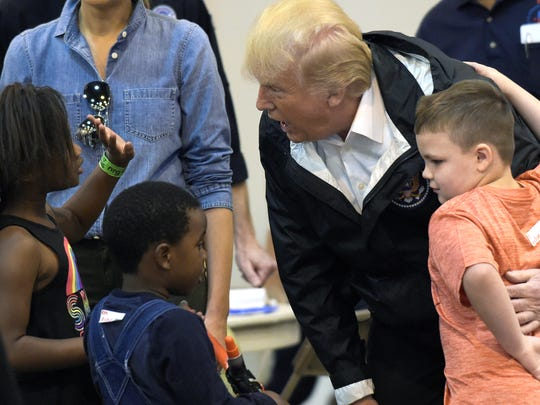 President Donald Trump talks with children impacted by Hurricane Harvey during a visit to the NRG Center in Houston, Saturday, Sept. 2, 2017.
