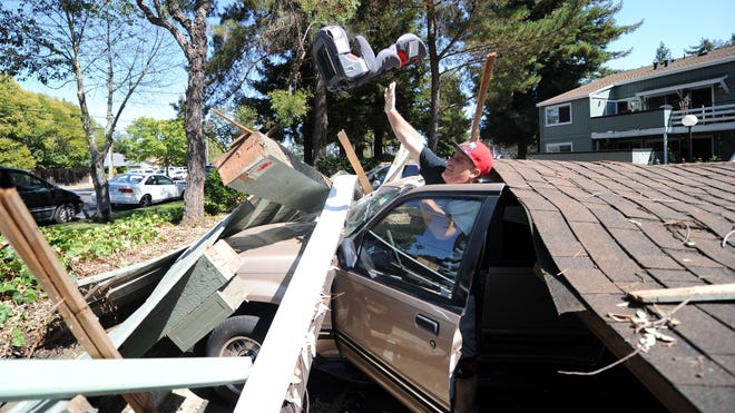 Karl Luchsinger removes a child's car seat from a vehicle after a carport collapsed during a 6.0 earthquake in Napa, Calif., on  Aug. 24, 2014.