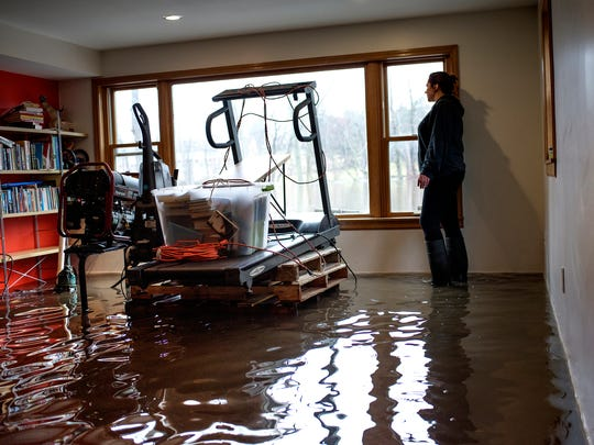 Jen Estill looks out the window at the Grand River from the flooded basement of her home on Friday, Feb. 23, 2018, on Tecumseh River Drive in Lansing. The water level reached the back of the home.