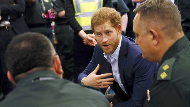 Britain's Prince Harry talks to staff as he visits the headquarters of the London Ambulance Service in London.