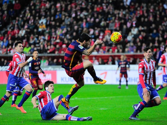 FC Barcelona's  Luis Suarez, center, tries to control the ball during their Spanish La Liga soccer match between Sporting de Gijon and FC Barcelona, at El Molinon stadium, in Gijon, northern Spain, Wednesday, Feb.17, 2016. (AP Photo/Alvaro Barrientos)