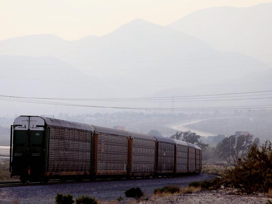A train travels west as haze hangs over the Coachella Valley. Climate change is exected to make smog and other forms of air pollution significantly worse, which could hit hardest in parts of the valley where asthma rates are already high.
