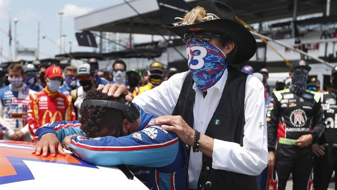 Driver Bubba Wallace is consoled by team owner Richard Petty, right, prior to the start of Monday's NASCAR Cup race at Talladega Superspeedway. Dozens of drivers showed their support of the circuit's only Black driver when it appeared a noose had intentionally been left in his garage.