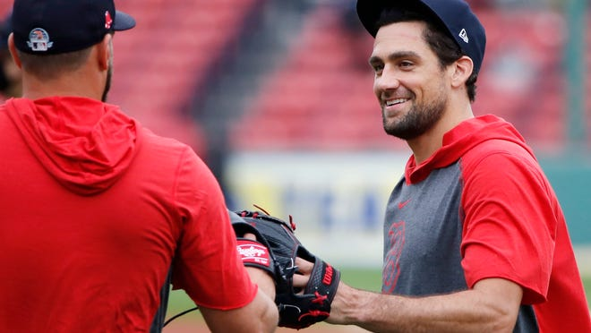 Red Sox right-hander Nathan Eovaldi taps gloves with a teammate during Friday's practice at Fenway Park.