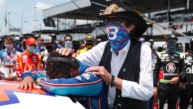 NASCAR driver Bubba Wallace is consoled by team owner Richard Petty, right, prior to the start of the NASCAR Cup Series at the Talladega Superspeedway in Talladega, Ala., Monday, June 22, 2020. In an extraordinary act of solidarity with Wallace, NASCAR's only Black driver, dozens of drivers pushed his car to the front of the field before Monday's race.