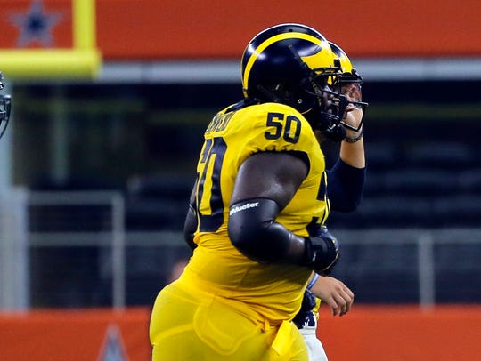 Michigan offensive lineman Michael Onwenu in the second