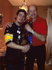 CJ Levchak, his dog Oscar and his father Charles. CJ and his father often bonded through watching sports.