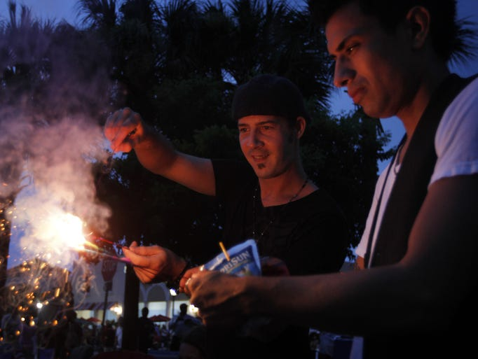 Ellsworth Bonia, center, and Adrian Ojeda light up sparklers during the Fourth of July celebration at Miromar Outlets in Estero on Saturday July 3, 2010. Rain throughout the evening did not keep thousands away from the festivities.