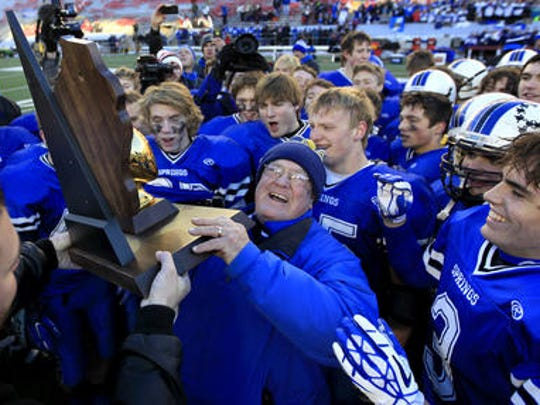 Bob Hyland holds up the state championship trophy WIAA Division 6 state championship trophy after the Ledgers defeated Darlington 37-28 last year in Madison in the 2015 Division 6 state title game.