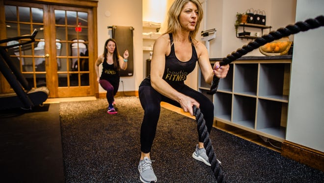 Taunton Boutique trainer Tina Bennet, right, does exercise with another trainer at the 9 Taunton Green location.