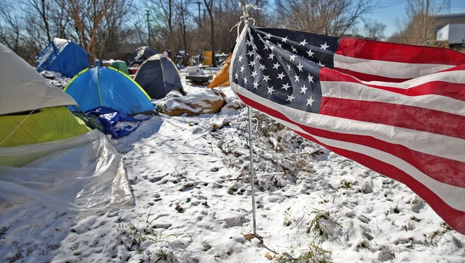 "An American flag waves in the cold wind at the homeless encampment referred to as ""The Jungle,"" Thursday, February 9, 2017.  Residents at the camp say they've been told they must leave the property in a week, but CSX officials say they have until spring to make the transition."