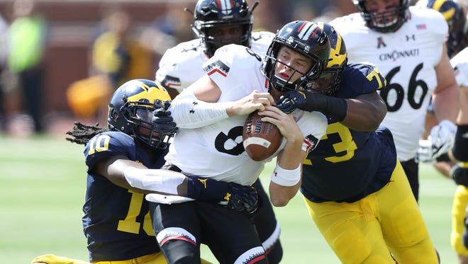 Michigan's Devin Bush sacks Cincinnati's Hayden Moore in the first quarter Saturday, September 9, 2017 at Michigan Stadium.