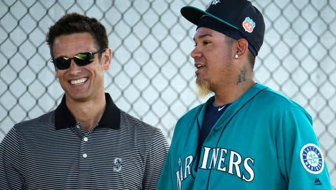 Seattle Mariners starting pitcher Felix Hernandez talks with general manager Jerry Dipoto after throwing during spring training baseball practice Saturday, Feb. 27, 2016, in Peoria, Ariz.