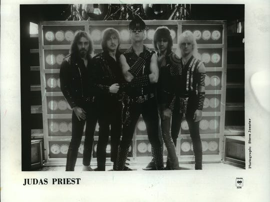 Rob Halford (center) with the other members of the rock band Judas Priest in 1983