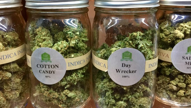 """Jars of marijuana flowers known as """"bud"""" offered for sale at a Denver-area marijuana store."""