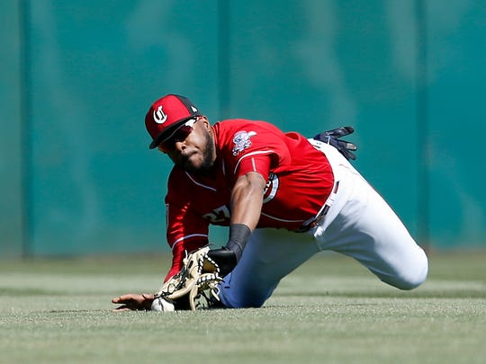 Cincinnati Reds outfielder Phillip Ervin (27) dives but is unable to cleanly catch a fly ball of the bat of Colorado Rockies designated hitter Brian Mundell (77) in the top of the second inning of the Spring Training game between the Cincinnati Reds and the Colorado Rockies at Goodyear Ballpark in Goodyear, AZ, on Saturday, Feb. 24, 2018.
