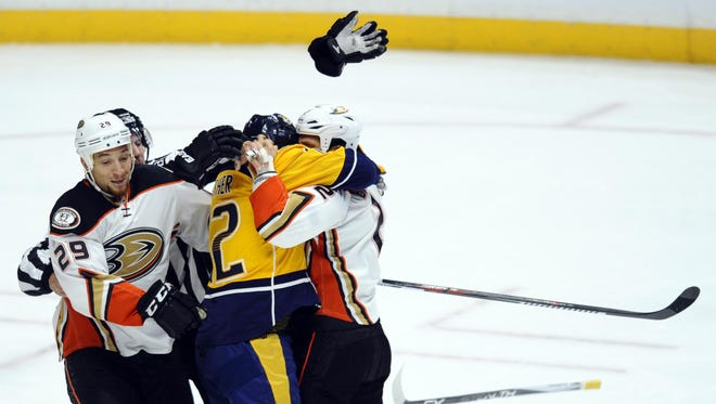 Ducks defenseman Kevin Bieksa (2) and Predators center Mike Fisher (12) fight in the first period Tuesday.