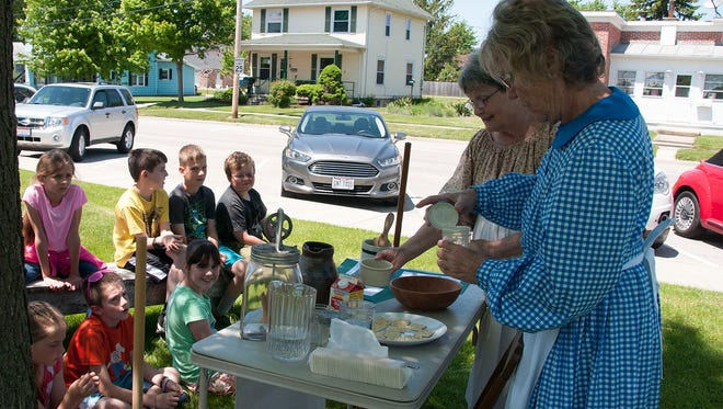 Volunteers Virginia Finken and Sharon Sprague teach third grade students from R. C. Waters  Elementary how to make homemade butter like the pioneers did when platting Oak Harbor in the 1860s.