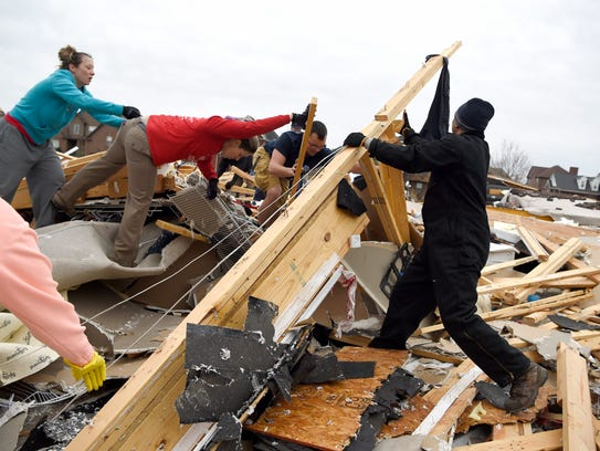 Neighbors help collect clothing and look for pets at a destroyed home Sunday morning after a fierce storm hit Saturday in the Farmington subdivision in Clarksville.