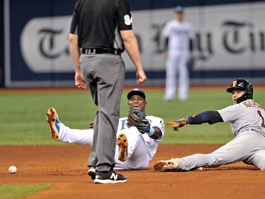 Umpire Lance Barrett looks on as Tampa Bay Rays shortstop Adeiny Hechavarria, center, laughs after Detroit Tigers' Jose Iglesias playfully took the ball from Hechavarria's glove and tossed it in the dirt when he was tagged out stealing second base during the sixth inning of a baseball game Tuesday, July 10, 2018, in St. Petersburg, Fla.