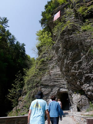 An American flag waves in the wind as Watkins Glen State Park visitors enter the gorge trail on Wednesday. The flag was unfurled to signify the official opening of the state park.