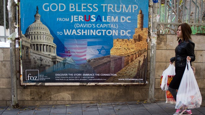 A woman walks past a poster praising U.S. President Donald Trump's recognition of Jerusalem as Israel's capital in Jerusalem on Thursday.