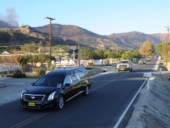 A hearse takes the remains of a Cal Fire engineer who