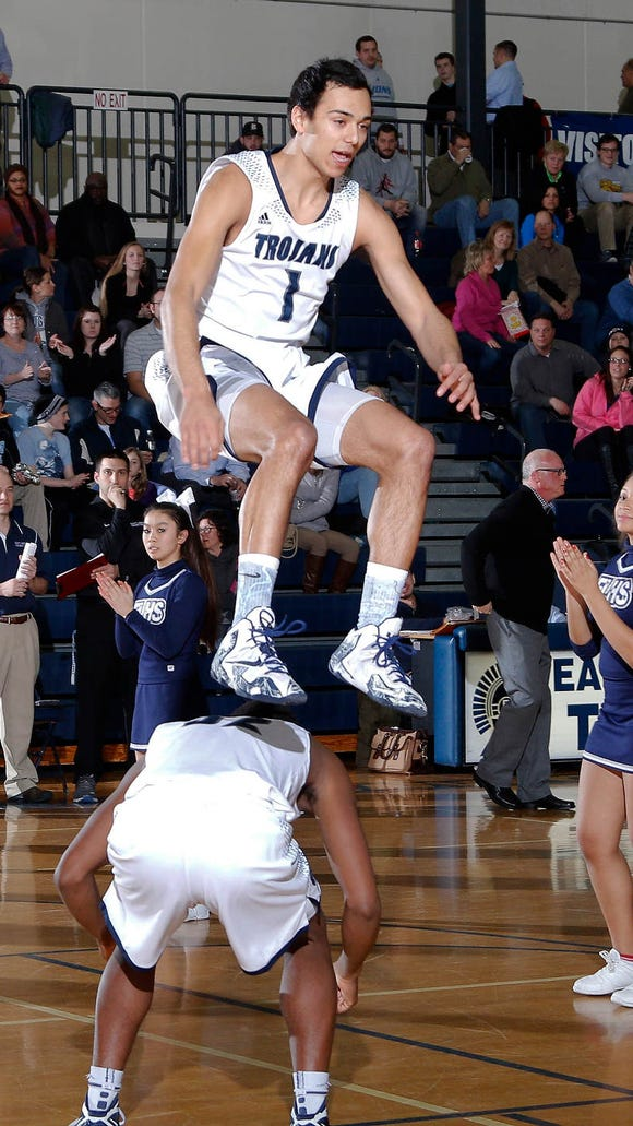 East Lansing's Mikhail Myles (1) leaps over teammate James D. Coles IV during introductions before their game agianst Lansing Catholic Tuesday, March 3, 2015, in East Lansing, Mich. East Lansing won 56-35.