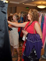 Kim Seymour picks out purple dresses to try on during the Love That Dress! fundraising gala Aug. 24 at Embassy Suites, benefitting PACE Center for Girls Lee County. She took the opportunity to find a dress for an upcoming purple themed party.