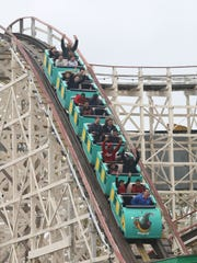 Riders enjoy the Dragon Coaster during the opening