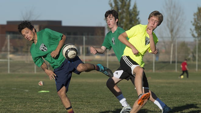Fossil Ridge soccer players play a game of keep away during practice Thursday. The No. 30 SaberCats are going to quarterfinals, taking on No. 6 Arapahoe on Saturday, after upsetting teams on the road for their last two games.