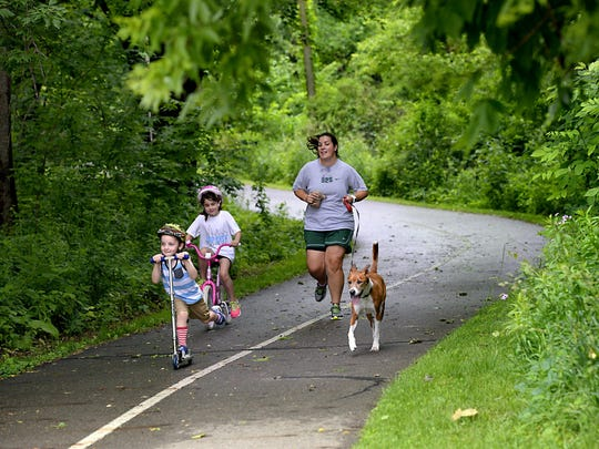 Helen Knull and her children Grace, 7, and Calum, 4, head down the River Trail in Lansing to Maguire Park. The family dog, Marvin, joins in the fun.