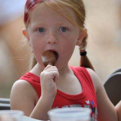 Paisley Green, 6, enjoys a corn dog at the Pensacola Sertoma 4th of July celebration Wednesday afternoon.