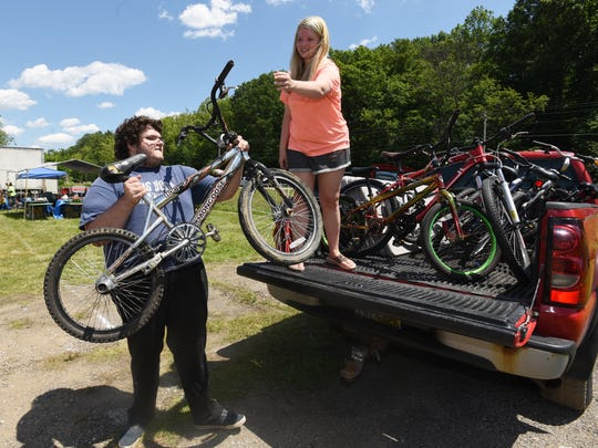 Nicole Crum and Sam Grubbs load bikes into a truck during the National Road Yard Sale on US 40 west of Zanesville on Friday. The two will return with bikes to sell on Saturday, near the former Route 40 Road House.